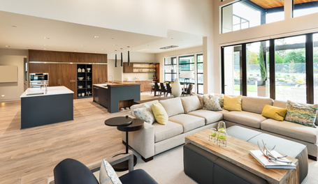 Beautiful staged living room interior in new luxury home with view of kitchen. Home interior with hardwood floors and open floorplan showing dining room, kitchen, and living room. Has high vaulted ceilings.